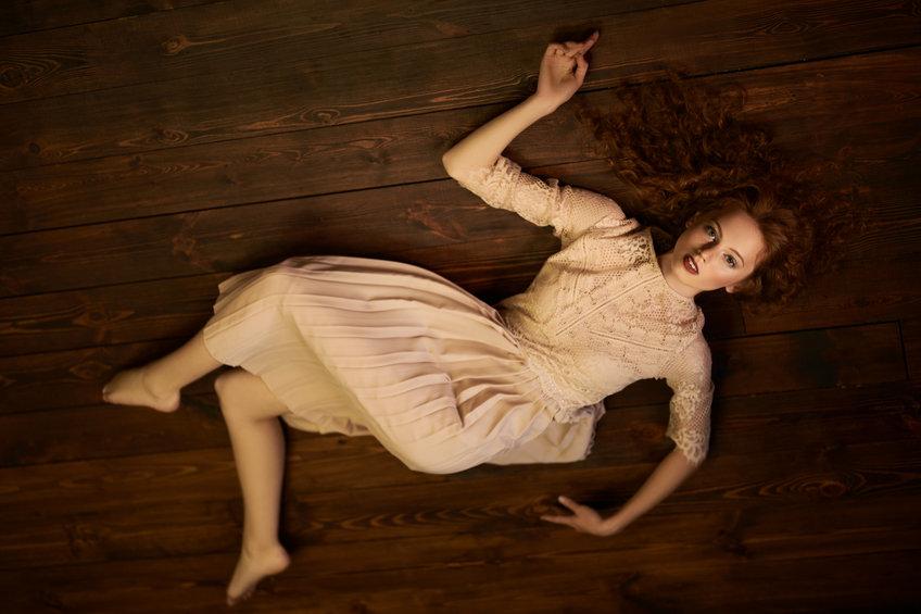 אישה שוכבת על פרקט בסלון - ענק הפרקטים